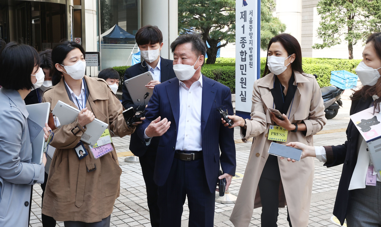 Kim Han-shin (C), the head of a research institute for economic cooperation between the two Koreas, answers reporters questions as a co-plaintiff of a lawsuit filed by a North Korean firm against South Korean companies over allegedly unpaid supply payments outside of the Seoul Central District Court on Tuesday. (Yonhap)