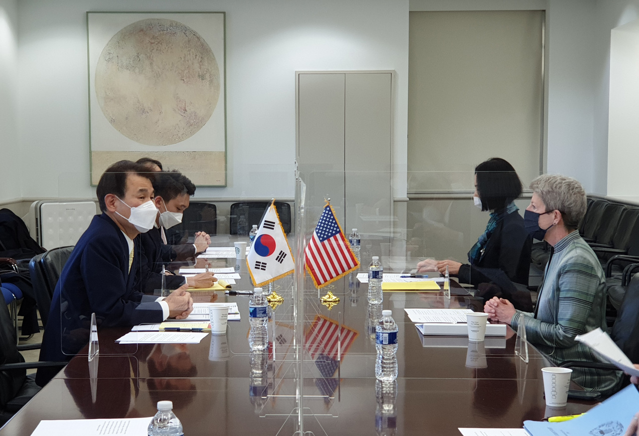 In this file photo, Jeong Eun-bo (L), South Korea's chief negotiator in defense cost-sharing talks with the United States, and his US counterpart, Donna Welton (R), engage in the latest round of negotiations in Washington on March 7, 2021, in this photo provided by the foreign ministry. (Ministry of Foreign Affairs)