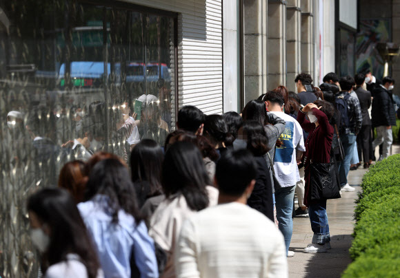Shoppers wait in a line outside a department store in Seoul. (Yonhap)