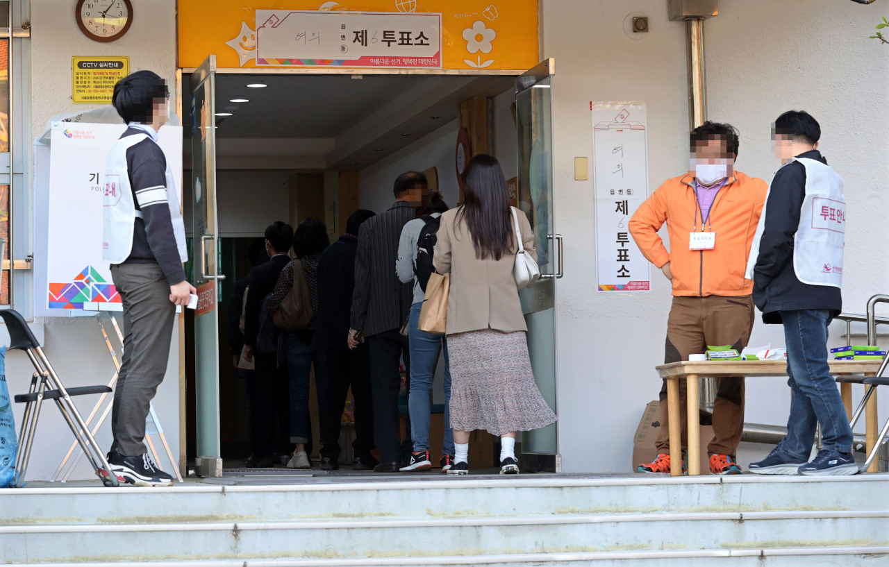 Seoul citizens line up to vote Wednesday by a poll booth installed at an elementary school in Yeongdeungpo-gu, western Seoul. (Yonhap)