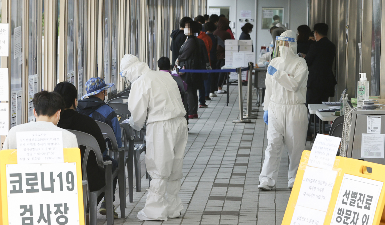 Citizens wait in a line to receive COVID-19 tests at a makeshift clinic in eastern Seoul on Wednesday. (Yonhap)