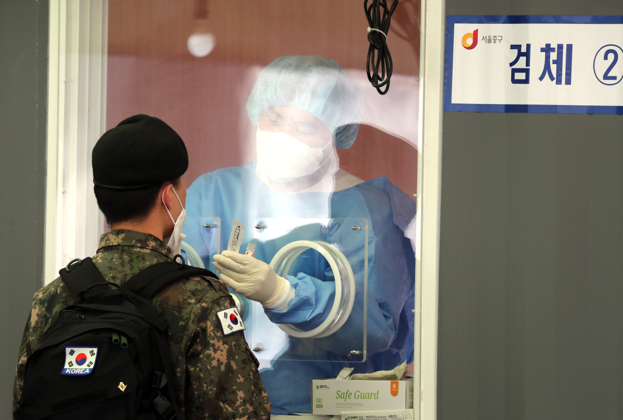 A service member undergoes a COVID-19 test at a temporary testing site in front of Seoul Station in central Seoul on Monday. (Yonhap)