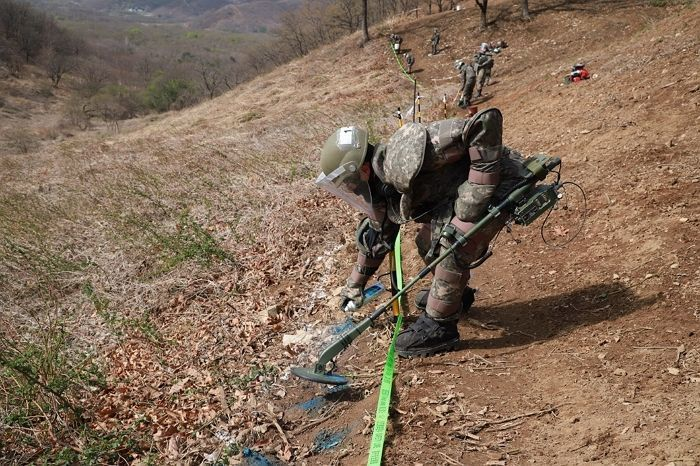 This undated photo, provided by the defense ministry on April 24, 2020, shows soldiers detecting mines at Hwasalmeori (arrowhead) Hill in the South Korean border town of Cheorwon next to the Demilitarized Zone bisecting the two Koreas, prior to the start of the excavation of the remains of soldiers killed in action there during the 1950-53 Korean War. This year's excavation work kicked off on April 20. (Ministry of National Defense)