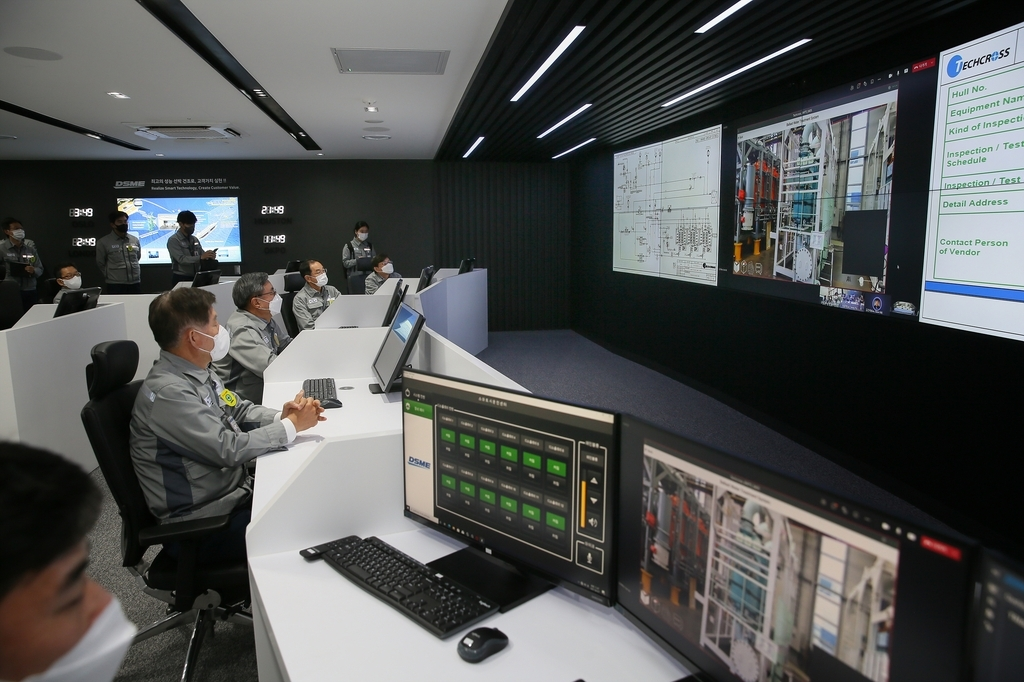This photo provided by Daewoo Shipbuilding & Marine Engineering Co. on Thursday, shows officials at the shipbuilder looking at screens at its Digital Production Center located at its Okpo shipyard on Geoje Island, 398 kilometers south of Seoul. (Daewoo Shipbuilding & Marine Engineering Co.)