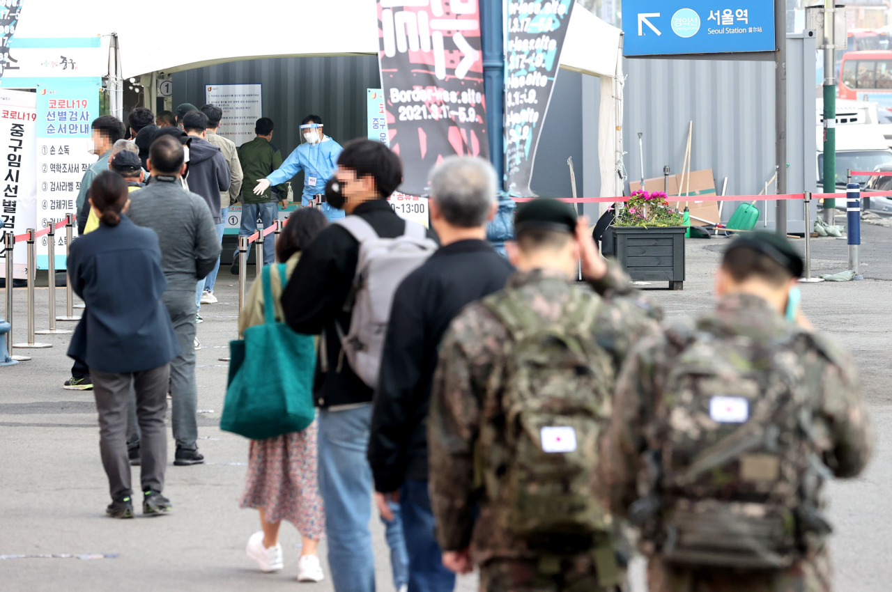 People stand in line to receive coronavirus tests at a makeshift clinic in front of Seoul Station on Wednesday. (Yonhap)