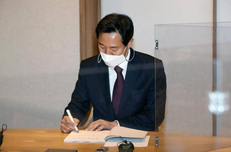 Oh Se-hoon of the main opposition People Power Party signs a document on taking office at Seoul City Hall on the first day of his tenure as Seoul mayor on Thursday. (Yonhap)