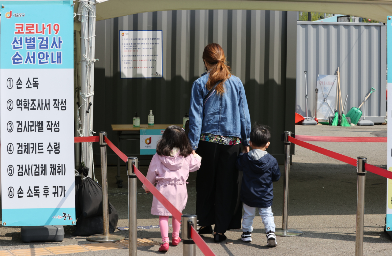 A citizen visits a makeshift clinic with her children in central Seoul to receive a COVID-19 test on Saturday. (Yonhap)