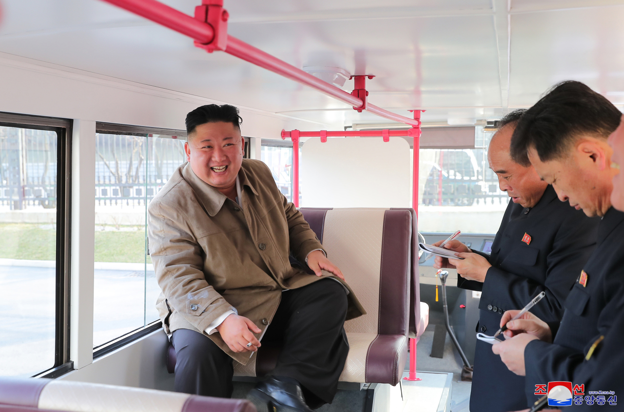 North Korean leader Kim Jong-un (L) sits inside a trial version of a double-decker bus in Pyongyang on March 25, 2021, as he inspects the trial versions of a passenger bus and a double-decker, developed by the Pyongyang General Passenger Service Enterprise and the Pyongyang City Bus Factory, in this photo released by the North's official Korean Central News Agency. Kim did not oversee the launch of a new type of missile that the North conducted the same day. (KCNA-Yonhap)