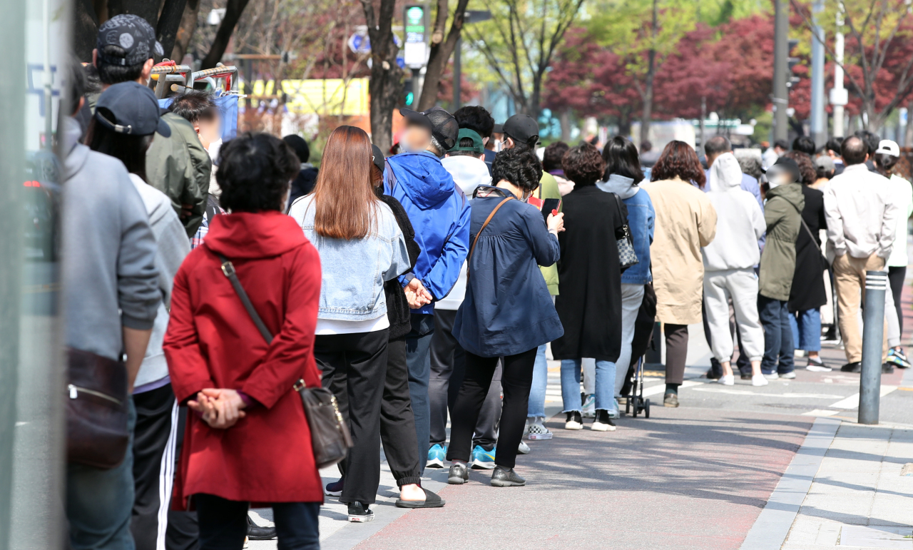 Citizens stand in line at a makeshift clinic in southern Seoul to receive COVID-19 tests on Sunday. (Yonhap)