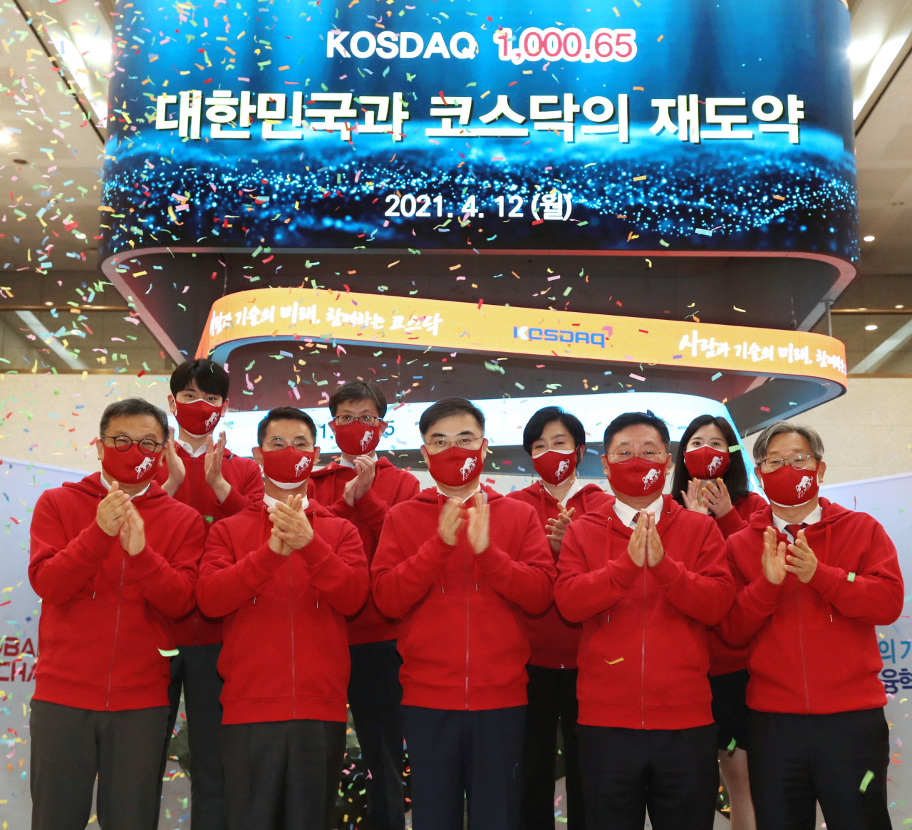 Kosdaq Listed Companies Association Chairman Chang Kyeong-ho (front row, second from left), Korea Exchange Chairman Sohn Byung-doo (front row, center), Korea Financial Investment Association Chairman Na Jae-chul (front row, fourth from left) and officials from the market operator celebrate South Korea's tech-heavy Kosdaq's closing above 1,000 points for the first time since Sept. 2000 at Korea Exchange's Seoul office on Monday. (KRX)