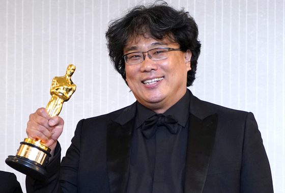 South Korean director Bong Joon-ho holds up his Oscar trophy at a press conference held at the London West Hollywood in Los Angeles on Feb. 9, 2020 (local time), after his black comedy film