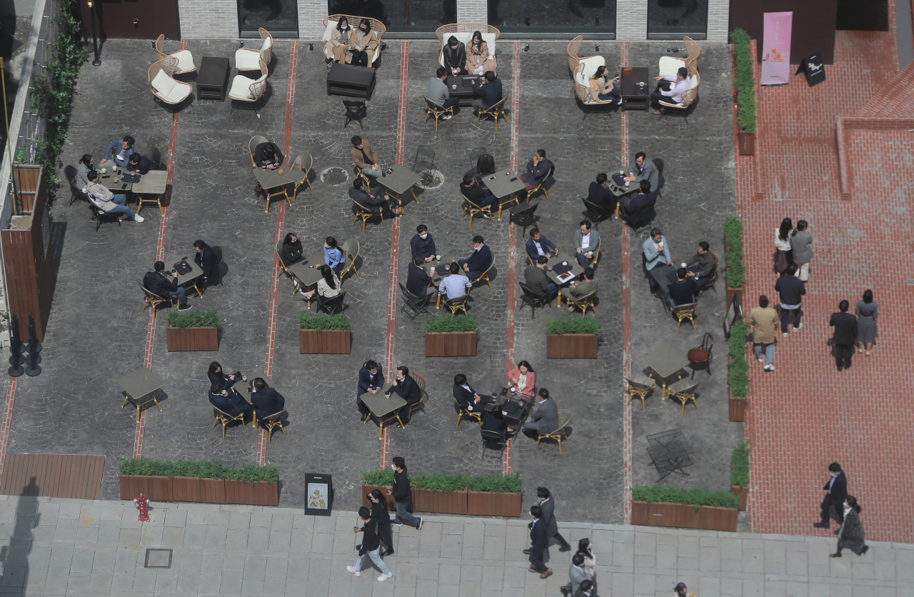 People enjoy coffee at outdoor terraces in downtown Seoul on Tuesday. (Yonhap)