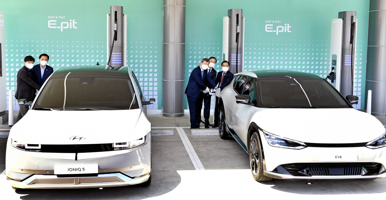 Dignitaries and company officials pose for photos at a ceremony to mark the opening of electric vehicle rapid charging stations at Hwaseong Rest Area on the Seohaean Expressway on Wednesday. (Yonhap)