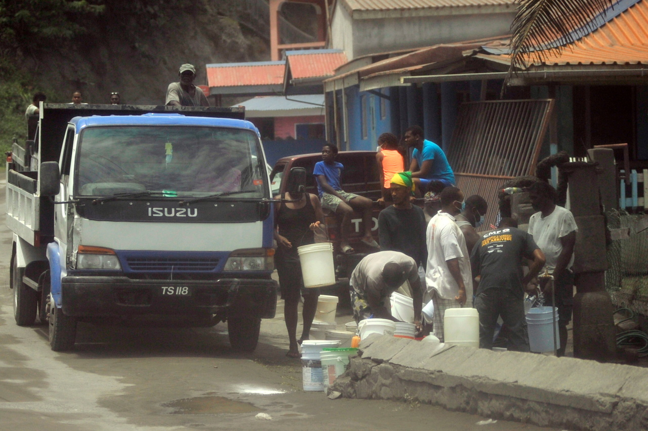 Local residents fill containers of water after a series of eruptions from La Soufriere volcano covered the area with a thick layer of ash in Biabou, Saint Vincent and the Grenadines. (Reuters-Yonhap)