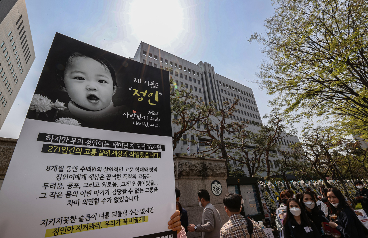 Citizens and activists hold a placard showing a picture of Jung-in, a baby girl who died from months of alleged physical abuse by her adoptive mother now facing trial for murder and other charges, during a rally calling for heavy punishment for the defendant in front of the Seoul Southern District Court. (Yonhap)
