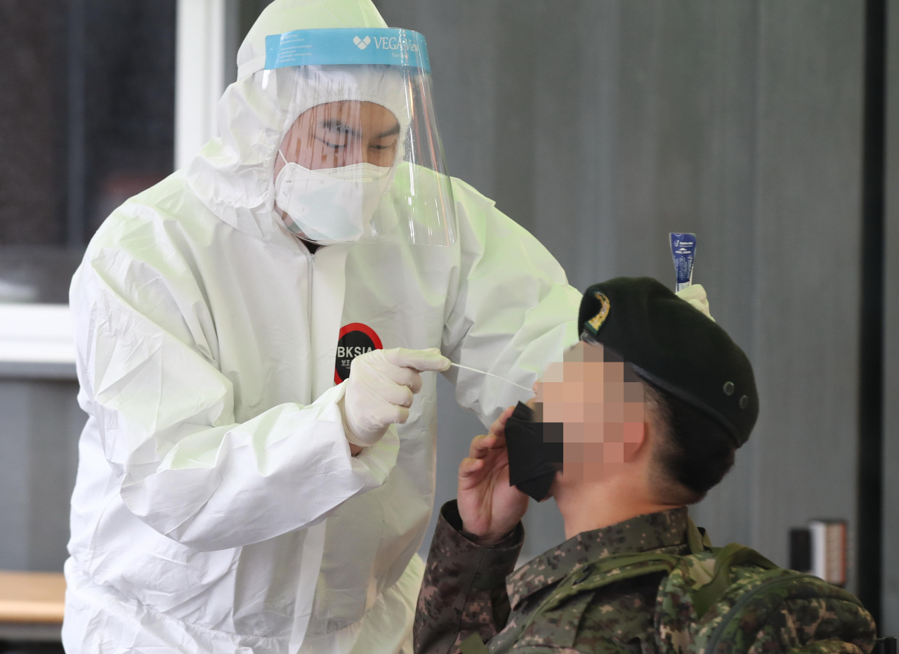 A service member undergoes a coronavirus test at a temporary COVID-19 test center at Seoul Station on March 1, 2021. (Yonhap)