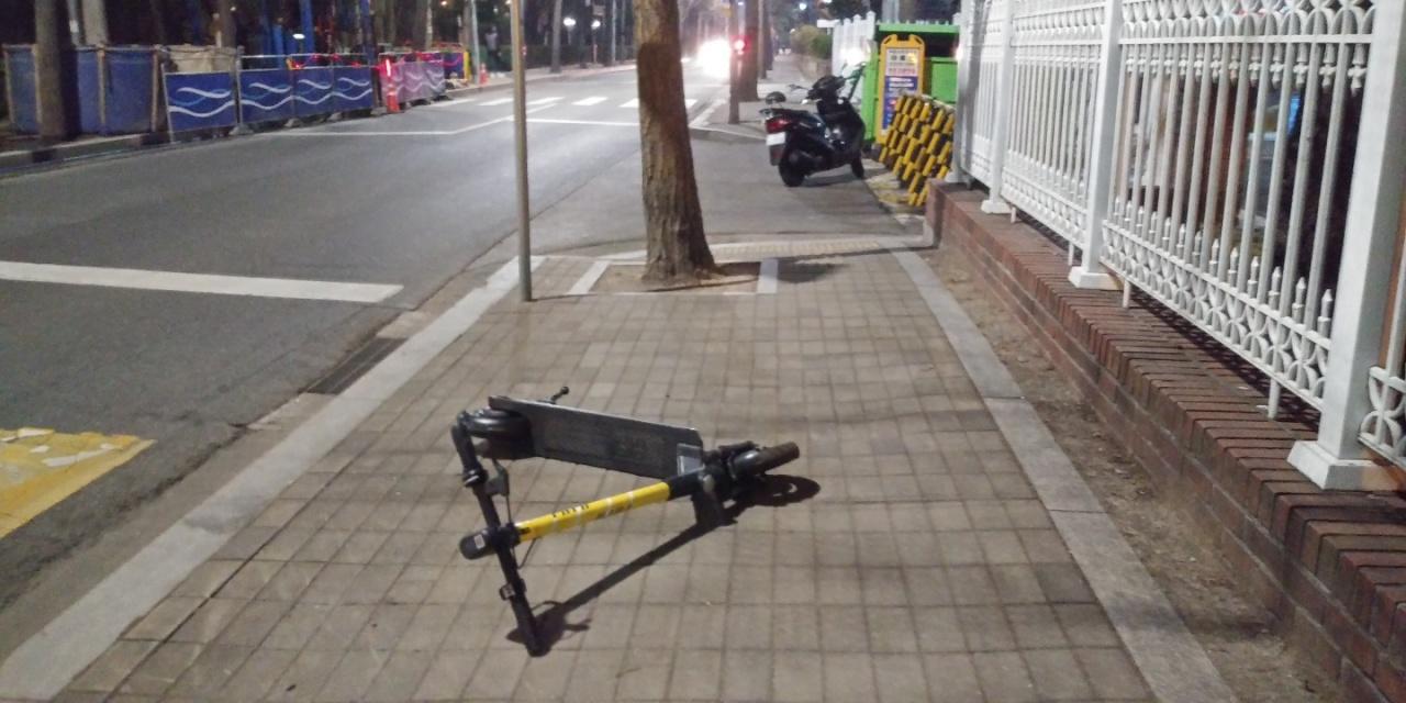 An e-scooter is left abandoned on a sidewalk. (Ko Jun-tae/The Korea Herald)