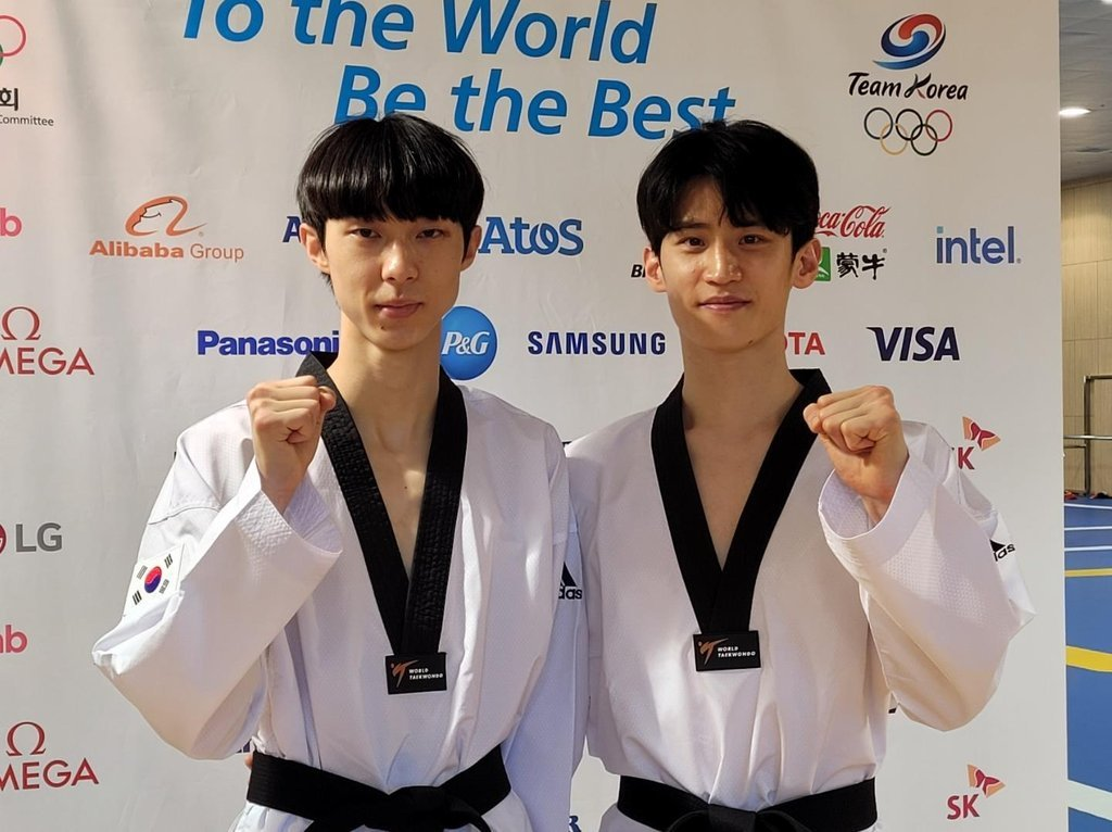 South Korean taekwondo practitioners Jang Jun (L) and Lee Dae-hoon pose for photos during an open practice session at the Jincheon National Training Center in Jincheon, 90 kilometers south of Seoul, on Wednesday. (Yonhap)