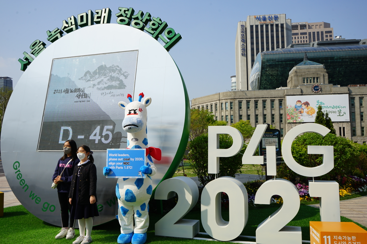 Kirini the blue-spotted giraffe holds up a sign in front of City Hall in central Seoul, calling on leaders to phase out coal by 2030 and keep their commitments under the Paris Agreement. (Korea Beyond Coal)