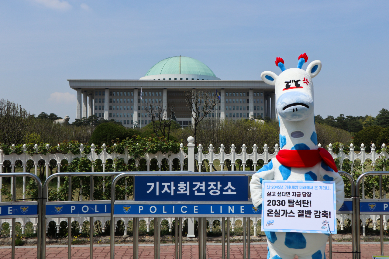 """Kirini the blue-spotted giraffe holds up a sign in front of the National Assembly in southwestern Seoul. It reads, """"2030 coal phaseout! Cut greenhouse gas emissions in half!"""" (Korea Beyond Coal)"""