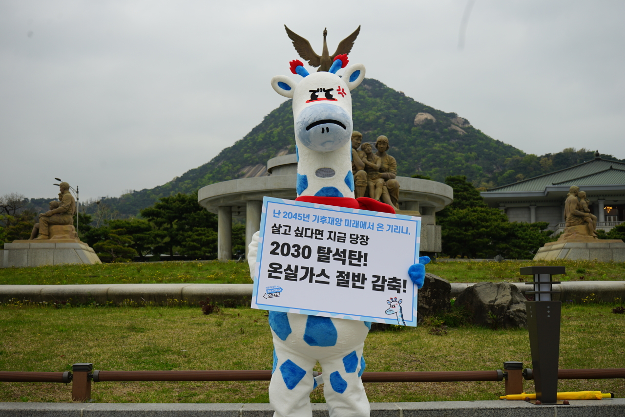 """Kirini the blue-spotted giraffe holds up a sign in front of the presidential office in central Seoul. It reads, """"2030 coal phaseout! Cut greenhouse gas emissions in half!"""" (Korea Beyond Coal)"""