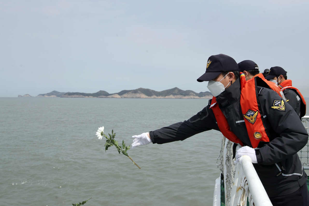 A victim's family member throws a flower into the waters near where the Sewol ferry sank off the coast of Jindo Island in South Korea on Friday. (Yonhap)