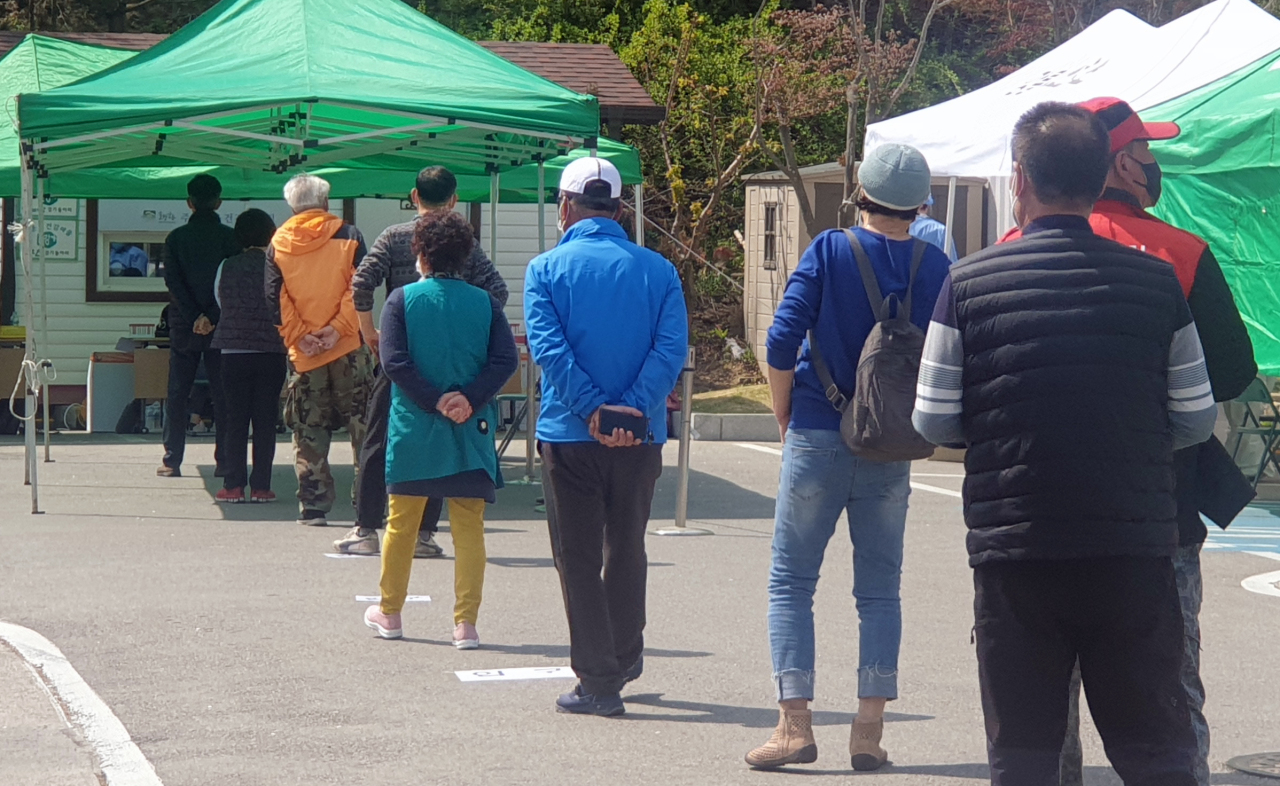 People wait in line Friday to get tested for COVID-19 at a testing center in Gangneung, Gangwon Province. (Yonhap)