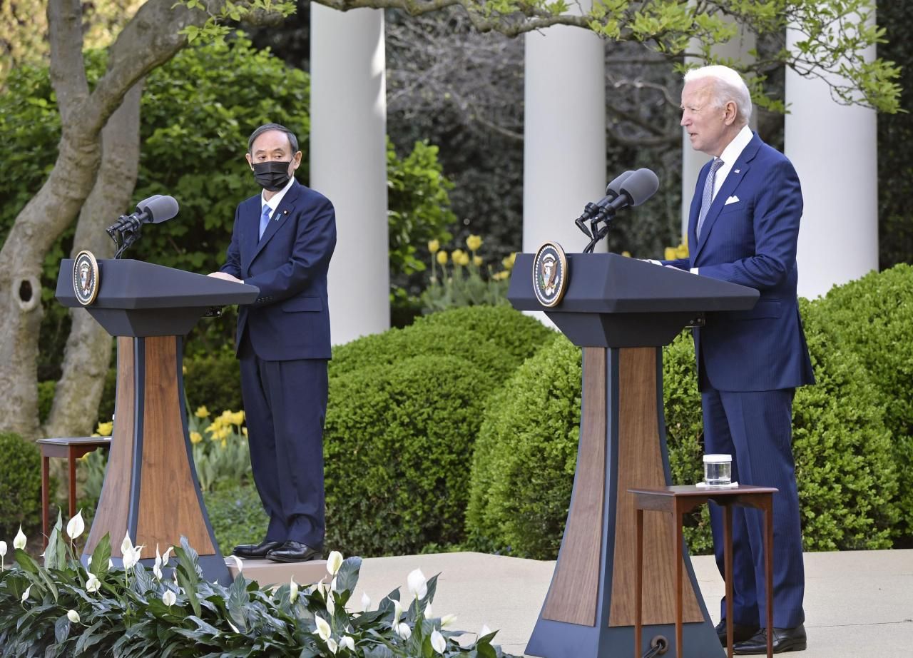 US President Joe Biden (right) and Japanese Prime Minister Yoshihide Suga (left) hold a joint press conference Friday after holding a bilateral summit in Washington. (Yonhap)