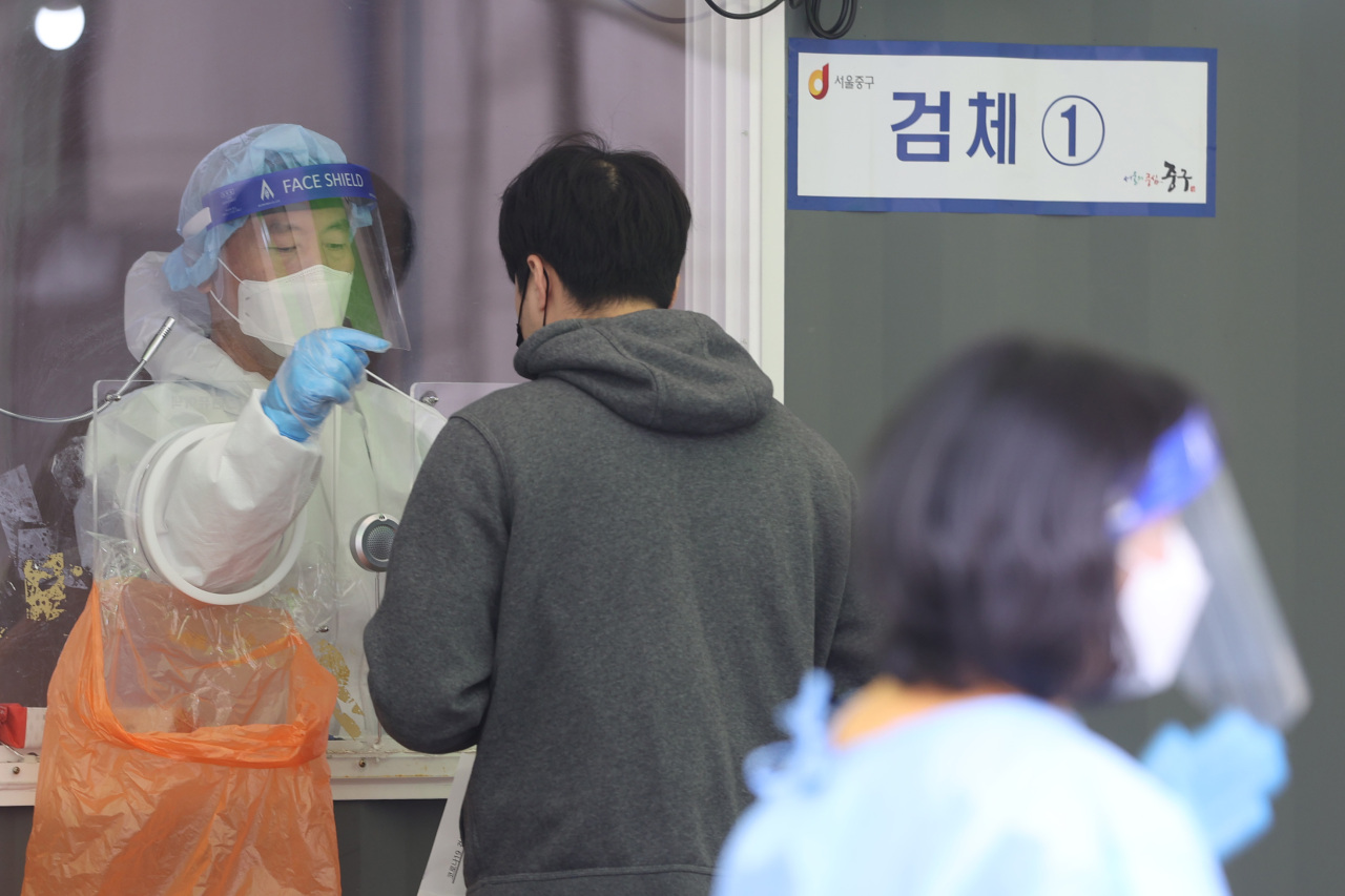 A medical worker collects a specimen from a person for COVID-19 testing at a temporary screening station in front of Seoul Station on Saturday. (Yonhap)