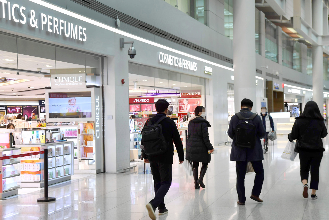 Passengers walk past duty free stores in Terminal 1 at Incheon Airport. (Yonhap)