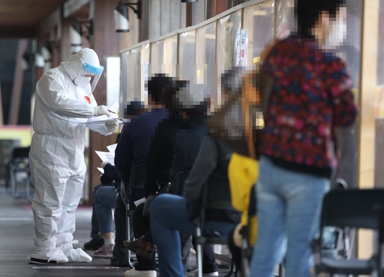 This photo taken on Sunday, shows a health worker clad in a protective suit guiding citizens at a makeshift COVID-19 testing clinic in Seoul. (Yonhap)