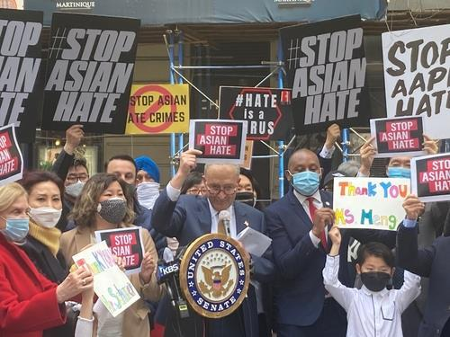 Senate Majority Leader Chuck Schumer (at podium) holds up a sign that says 'Stop Asian Hate' at a press event in Koreatown, Manhattan, on Monday. (Yonhap)