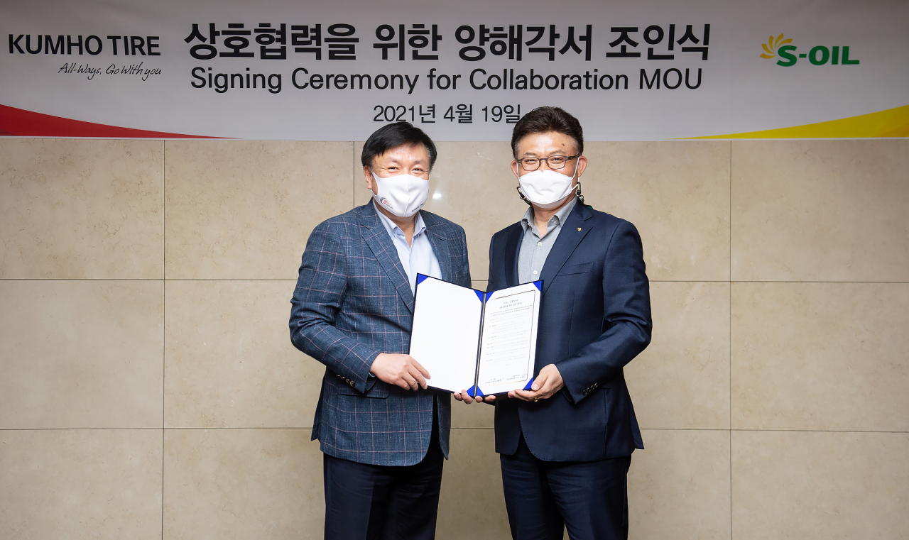 S-Oil Head of Marketing Ahn Jong-bum (right) and Kumho Tire Head of Sales and Marketing Kim Sang-yub pose for a photo after signing a partnership at S-Oil headquarters in Mapo-gu, western Seoul, Monday. (S-Oil)