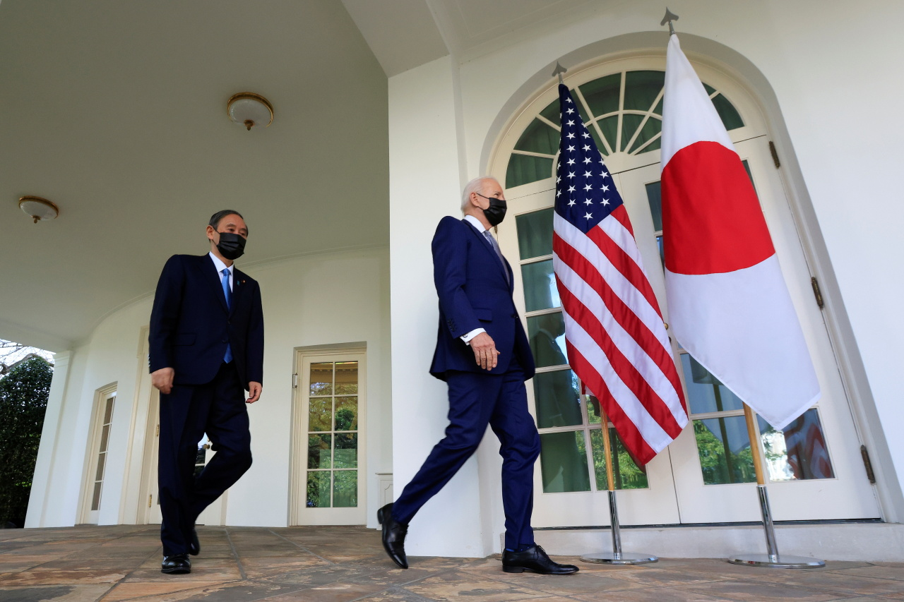 US President Joe Biden walks out of the Oval Office with Japan`s Prime Minister Yoshihide Suga ahead of a news conference at the White House in Washington, Friday. (Reuters-Yonhap)