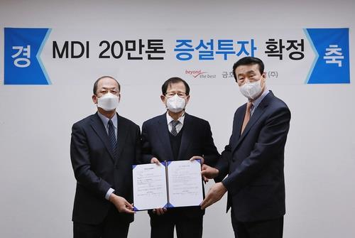 Park Chan-koo (C), chairman of South Korea's Kumho Petrochemical, and On Yong-hyun (R), CEO of Kumho Mitsui Chemicals, pose for a photo after approving a 400 billion-won ($358 million) investment plan to expand a methylene diphenyl diisocyanate (MDI) factory in Yeosu, 455 kilometers southwest of Seoul, on Wednesday, in this photo provided by Kumho Petrochemicals. (Kumho Petrochemicals)