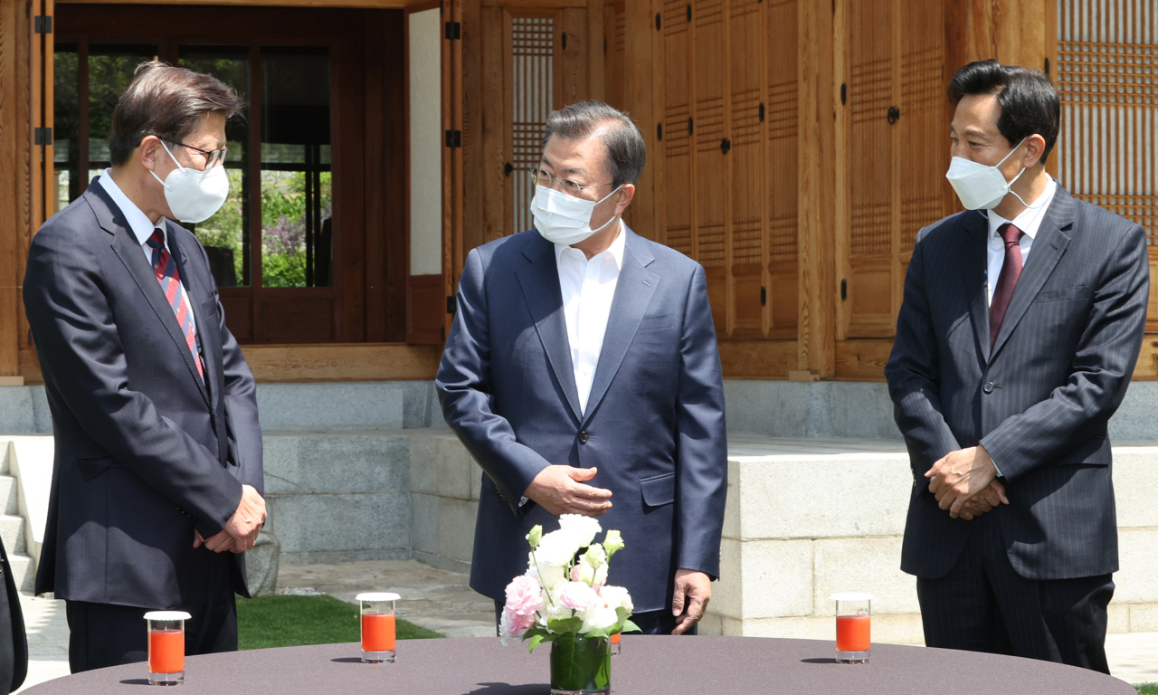 President Moon Jae-in greets Seoul Mayor Oh Se-hoon (right) and Busan Mayor Park Heong-joon (left) at the Sangchunjae guesthouse of the presidential compound on Wednesday, prior to their luncheon meeting. (Yonhap)