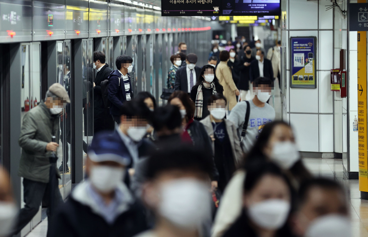 Masked commuters photographed at a Seoul subway station. (Yonhap)