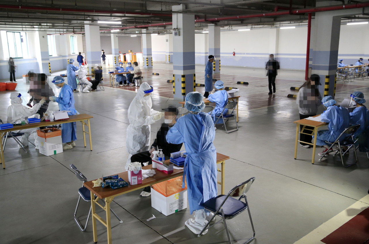 This photo taken on Wednesday, shows health workers clad in protective suits conducting tests on citizens at a makeshift virus testing clinic set up in a church's parking lot in Gwangju. (Yonhap)