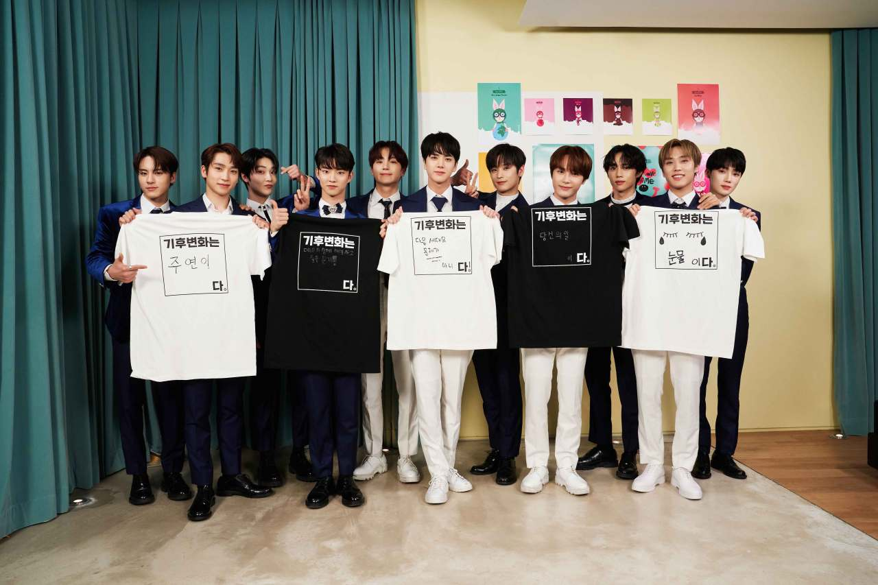 K-pop stars pose for a photo in T-shirts explaining what climate change means to them. (Climate Media Hub)