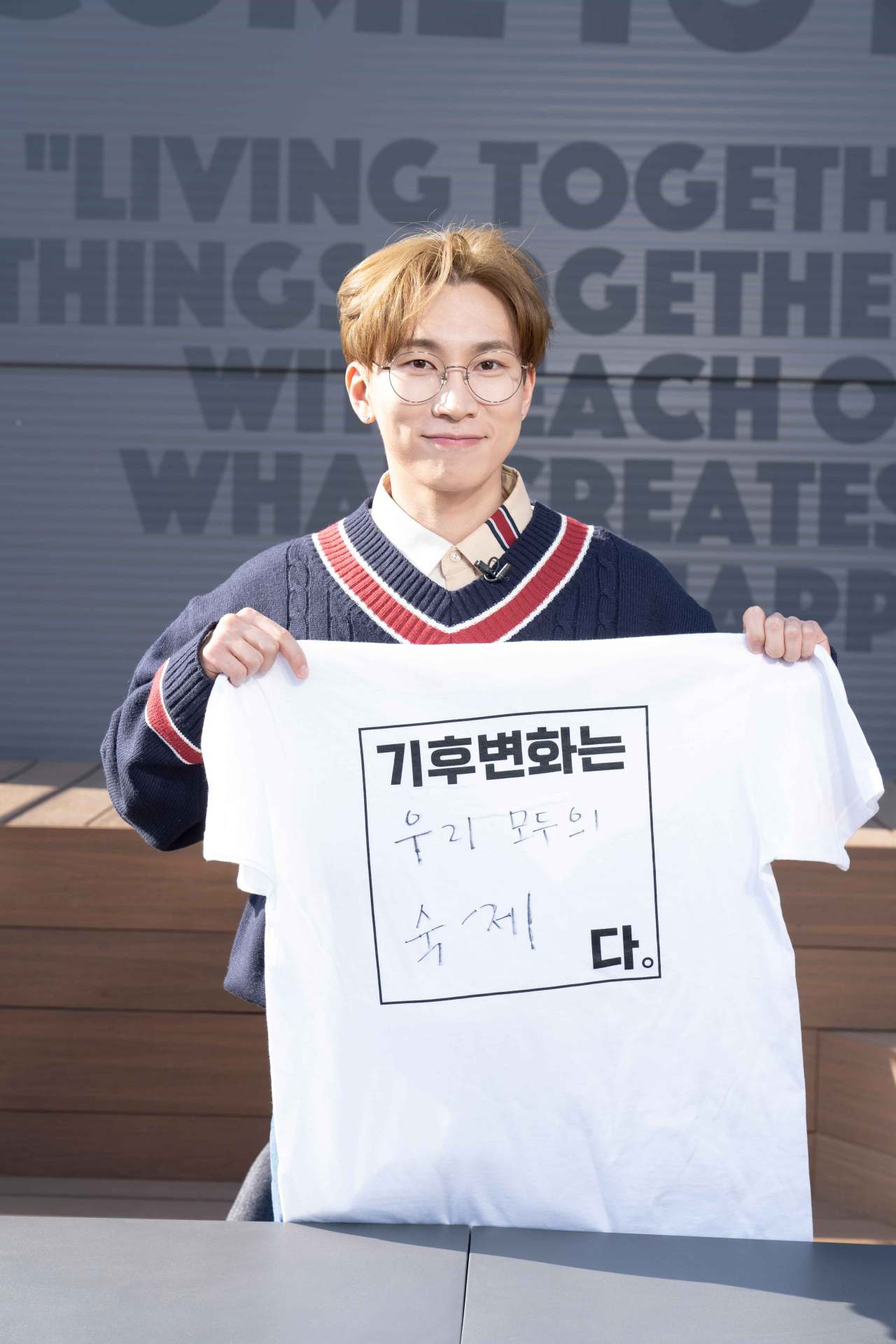 """Seo Eun-kwang of BTB holds up a T-shirt that reads, """"Climate change is everyone's homework."""" (Climate Media Hub)"""