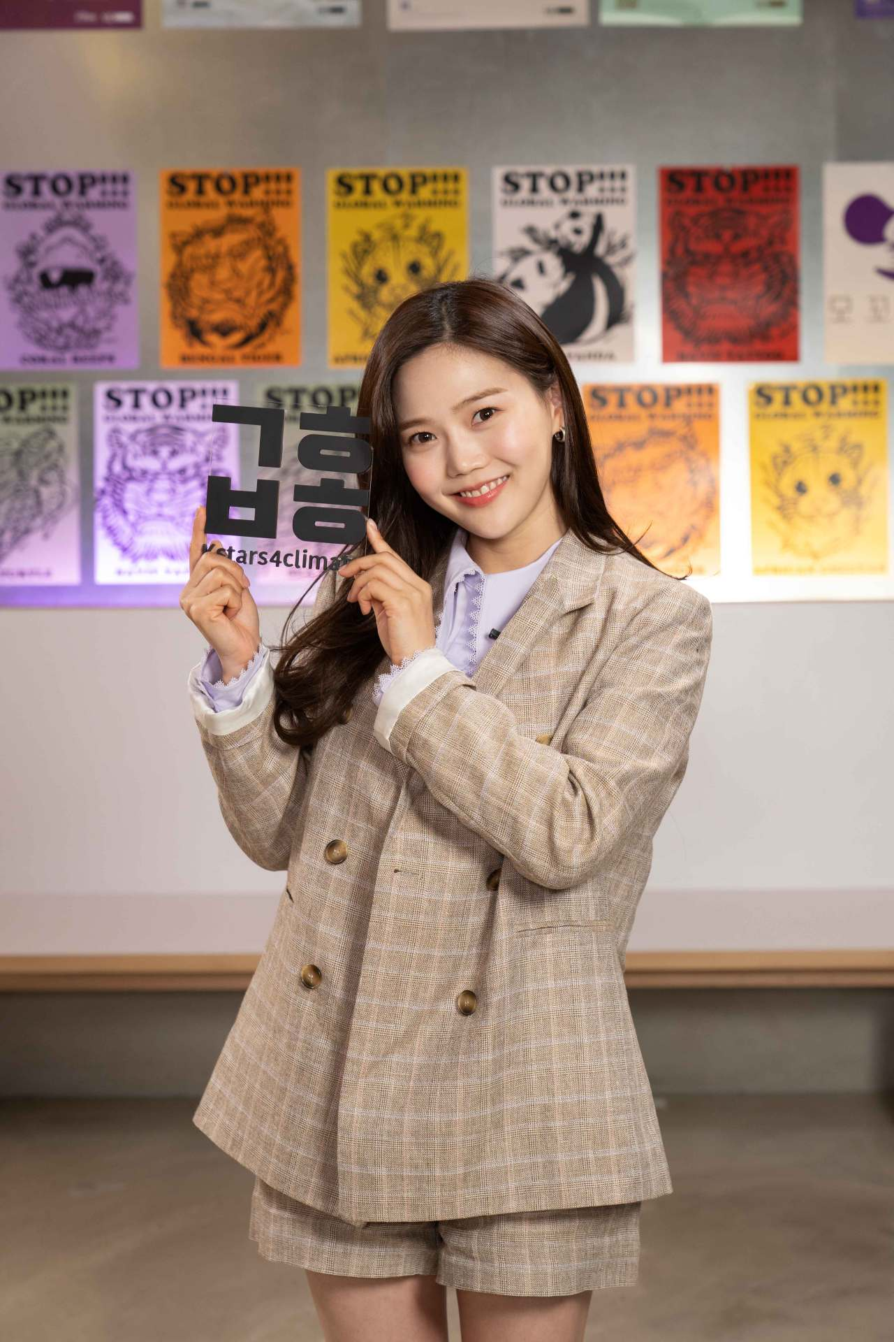 Hyojung from girl band Oh My Girl holds a sign showing the Hangeul abbreviation for