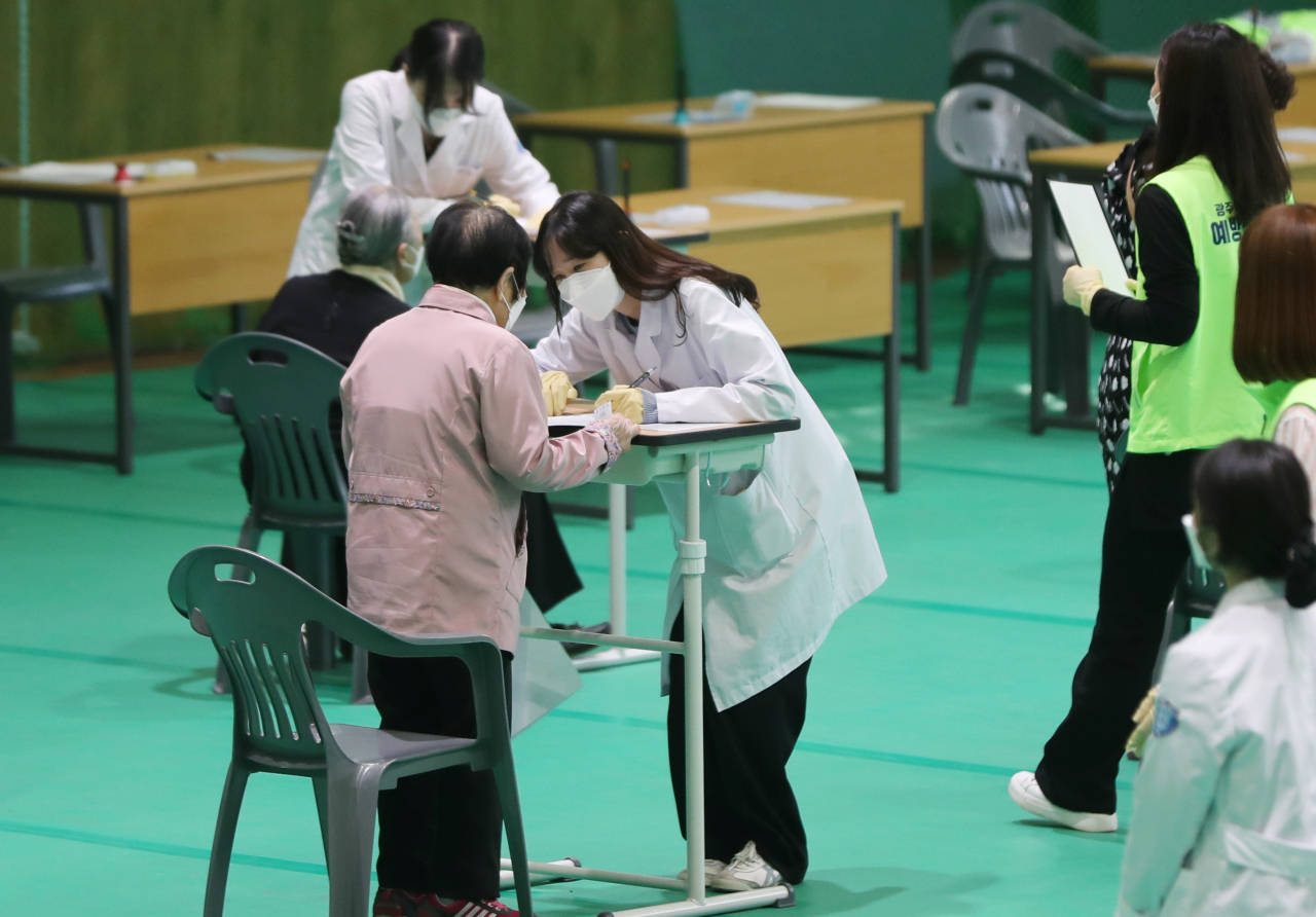 Health care workers on Monday examine people prior to vaccination at a center in Gwangju. (Yonhap)