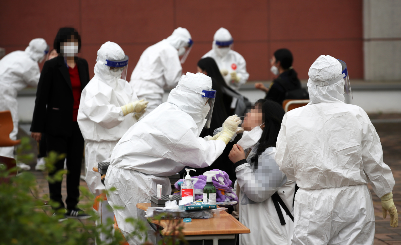 This photo, taken on Thursday, shows health workers clad in protective suits collecting samples from students for COVID-19 tests at a makeshift virus testing clinic in Gwangju, 329 kilometers south of Seoul. (Yonhap)