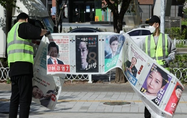 Officials remove election posters after the April 7 by-elections in Seoul. The above picture is not directly related to the article. (Yonhap)