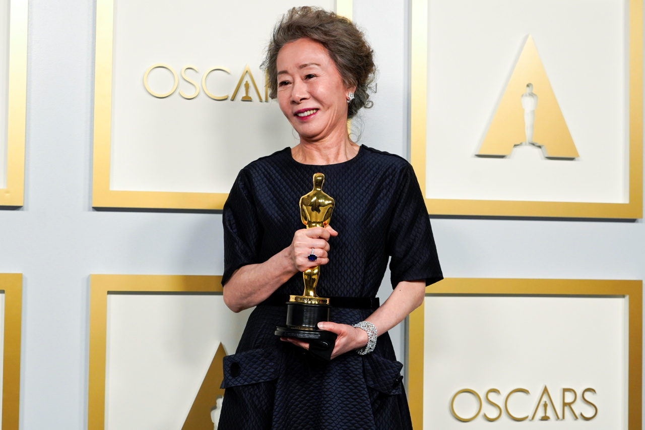 Youn Yuh-jung poses for photos after winning the best supporting actress award at 93rd Academy Awards in Los Angeles, on Sunday. (Reuters-Yonhap)