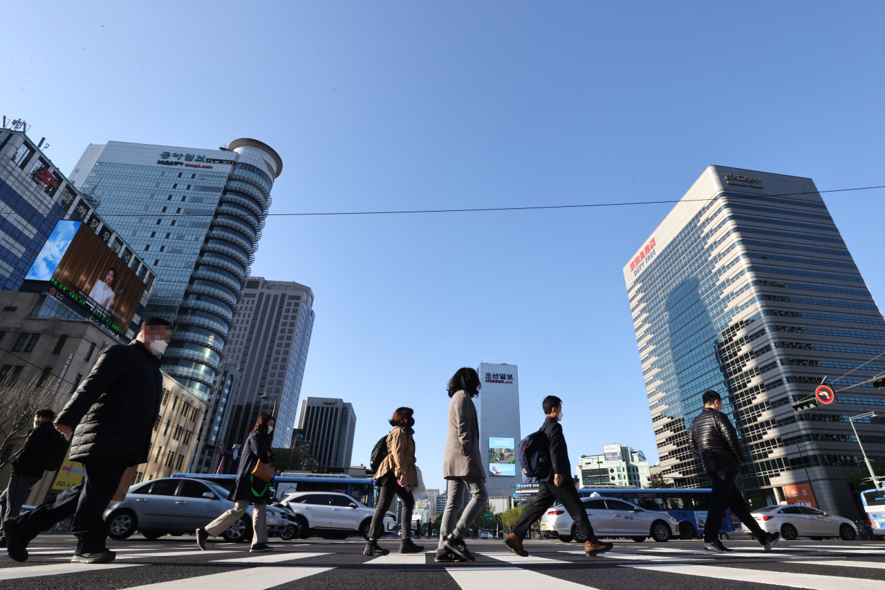 Pedestrians cross the street near Gwanghwamun Square in central Seoul in this photo taken on April 14. (Yonhap)