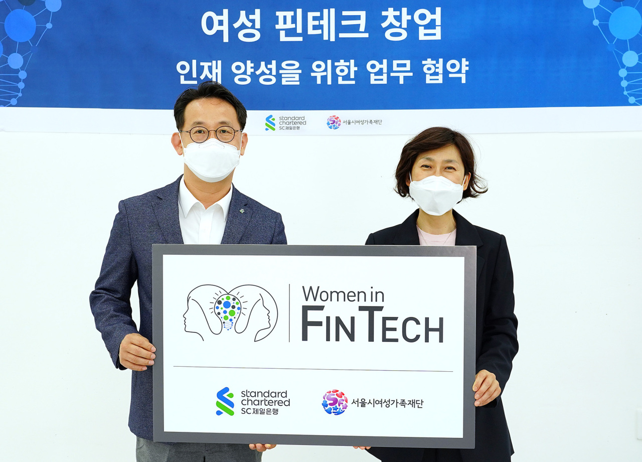 Choi Ki-hoon (left), head of the marketing and communications division at SC Bank Korea, and Baek Mi-soon, CEO of the Seoul Foundation of Women and Family, pose for a photo after signing a memorandum of understanding at Space Sallim in Seoul, Monday. (SC Bank Korea)