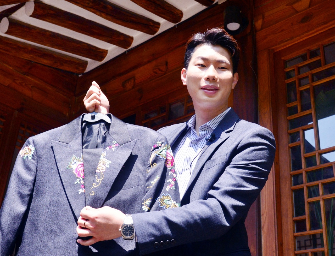 Designer Kim Ri-eul poses with one of his hanbok suits during an interview with The Korea Herald in Seoul. (Park Hyun-koo/The Korea Herald)