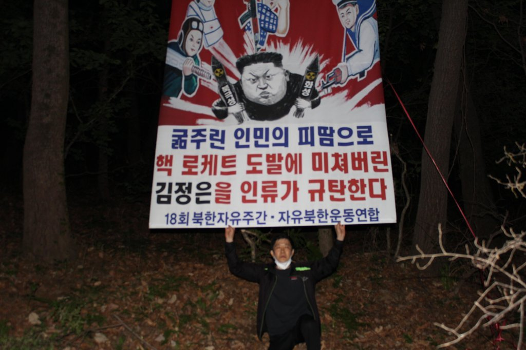 Park Sang-hak, who leads Fighters for a Free North Korea, holds a leaflet criticizing North Korean leader Kim Jong-un for starving his own people by developing nuclear weapons in this photo provided by the group. (Fighters for a Free North Korea)