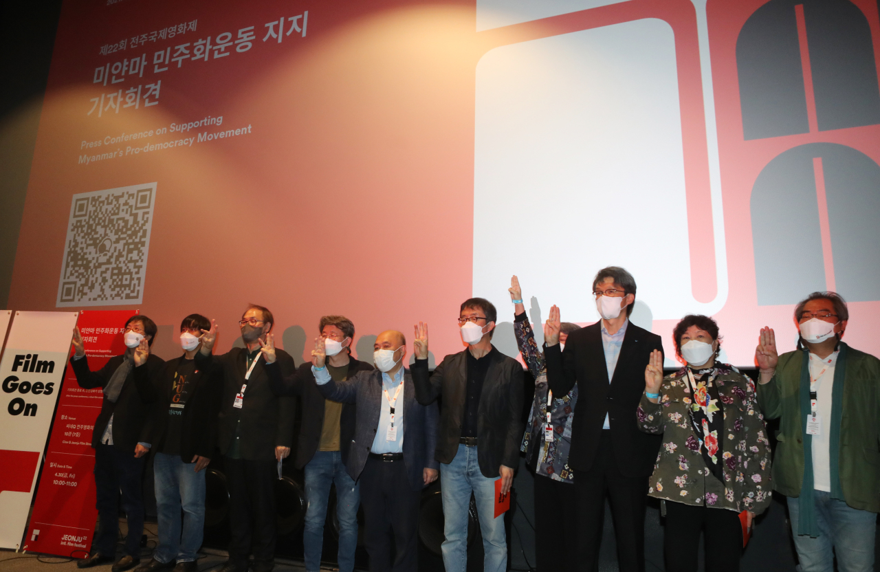 Participants raise three-finger salutes at a press conference on supporting Myanmar's pro-democracy movement at CINE Q Jeonju Film Street on Friday. (Yonhap)